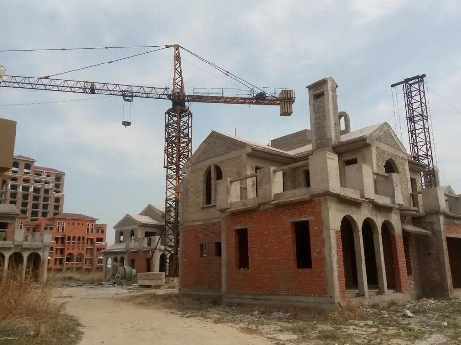 塔吊下的多栋烂尾别墅。来源:中国房地产报。